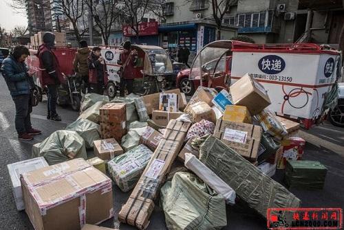 快递员站在成堆的包裹旁边